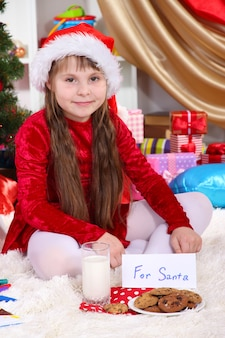 Beautiful little girl with milk and cookies for santa claus in festively decorated room