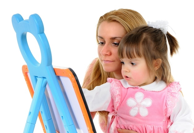 Beautiful little girl with mom draw together on the blackboard