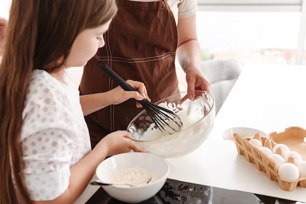 Красивая маленькая девочка с мамой печет тесто на кухне дома и замешивает тесто ручным миксером