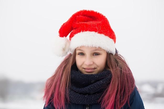 야외에서 산타 모자에 분홍색 머리를 가진 아름 다운 소녀 프리미엄 사진