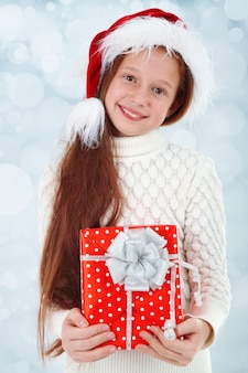 明るい背景にプレゼントボックスを持つ美しい少女