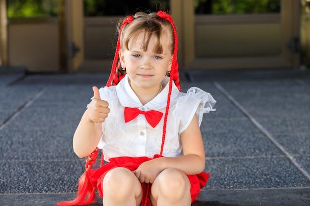 Красивая маленькая девочка с красными косичками и галстуком-бабочкой. ребенок показывает палец вверх. фото высокого качества