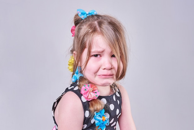 Beautiful little girl with a sad expression and tears in her eyes