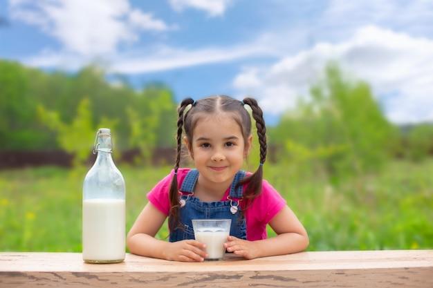 2つのおさげ髪の美しい少女は、テーブルに座って、ミルクと笑顔のガラスを保持しています。