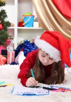 美しい少女は、お祝いに飾られた部屋でサンタクロースに手紙を書きます