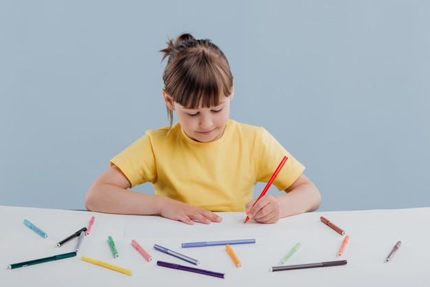 Beautiful little girl in a yellow t-shirt coloring