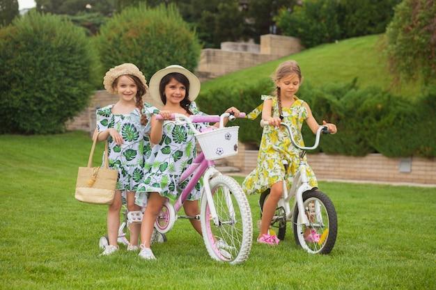 Красивые маленькие девочки едут на велосипеде по парку. природа, образ жизни