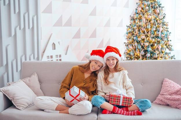 거실에서 크리스마스에 선물을 가진 아름다운 어린 소녀