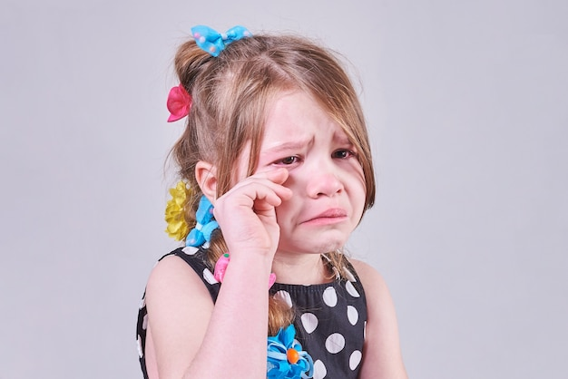 A beautiful little girlwith a sad expression cries and wipes her tears with her hands