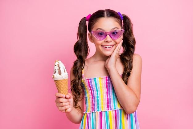Beautiful little lady hold big cone ice cream hand on cheek