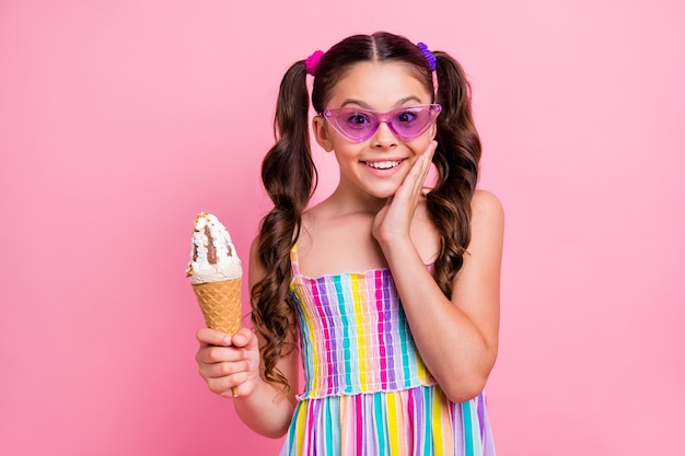 Красивая маленькая леди держит руку на щеке с большим рожком мороженого