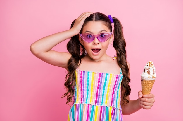 Красивая маленькая леди две милые держат большой конус мороженого