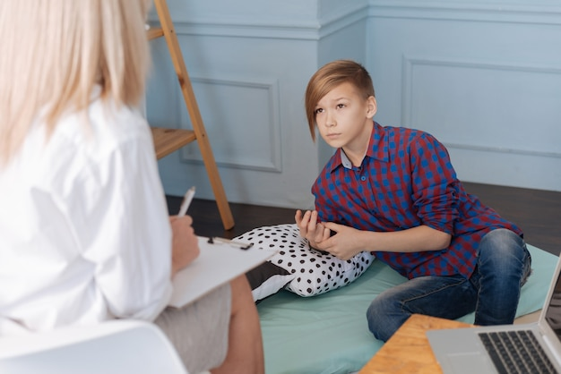 Beautiful little man-child with brown hair visiting psychotherapy resting while wearing checked shirt.