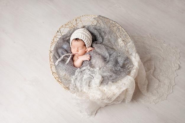 ニットの格子縞のバスケットで2週間眠っている美しい小さな新生児。かなり生まれたばかりの赤ちゃんの肖像画