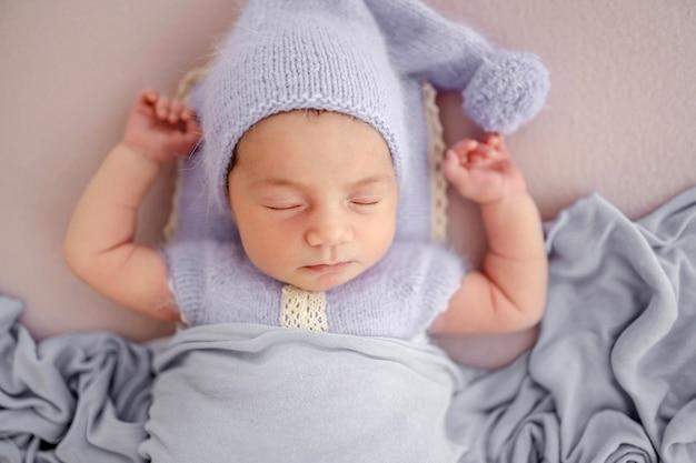 니트 의상을 입고 모자를 쓰고 스튜디오에서 담요 아래 손을 위로 들고 자고 있는 아름다운 갓난 아기 소녀. 귀여운 유아 아이 낮잠