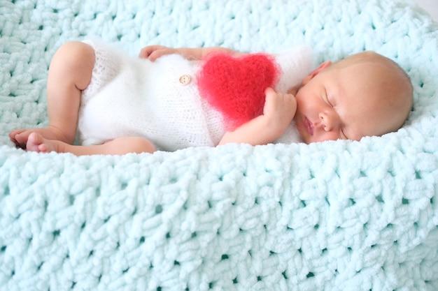 青い毛布で寝ている美しい小さな生まれたばかりの赤ちゃん