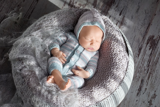 20日間の美しい小さな新生児はバスケットで眠ります。かなり生まれたばかりの男の子の肖像画