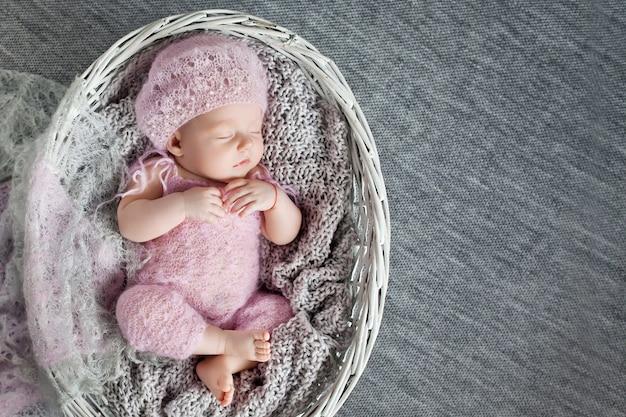 美しい小さな新生児の女の子は、1ヶ月の編み枝細工のバスケットで眠ります。コピースペース