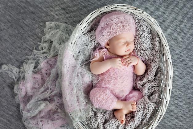 美しい小さな新生児の女の子1ヶ月は編み枝細工のバスケットで眠る