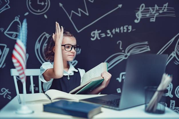 Красивая маленькая школьница сидит за партой и учится онлайн с ноутбуком на черном фоне с ...