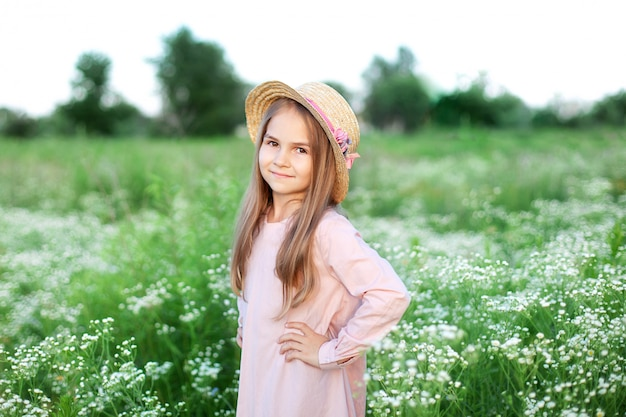Beautiful little smiling girl in pink dress and straw hat in field of daisies. cute child in field of blooming chamomile in summer. wildflowers.