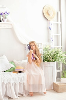 Beautiful little smiling girl sits on bed in bedroom with bouquet of summer flowers. girl holding a bouquet of lavender.