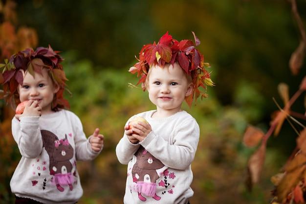 가을 정원에서 사과를 들고 있는 아름다운 쌍둥이 소녀들 사과를 가지고 노는 어린 소녀들