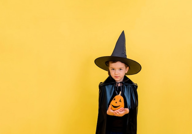 Beautiful little witch in a hat with a decorated pumpkin on a yellow isolated