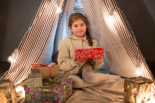 Красивая маленькая женщина сидит с подарком в руках