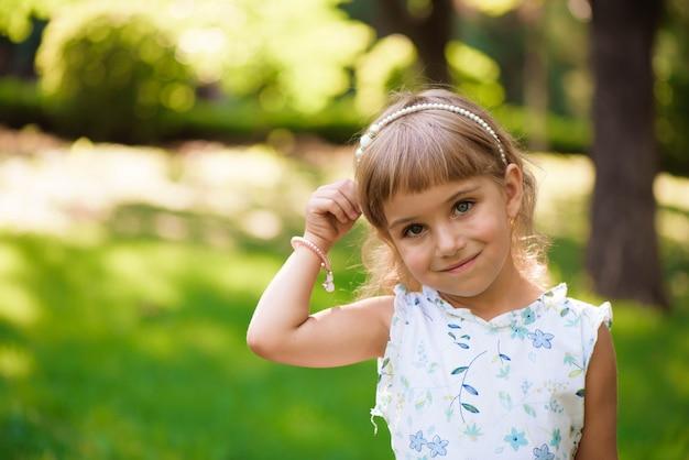 公園の屋外の美しい小さな少女。