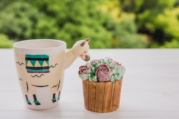 Beautiful llama shaped trendy cup with hot drink and two cupcakes on white wooden table with bright greens