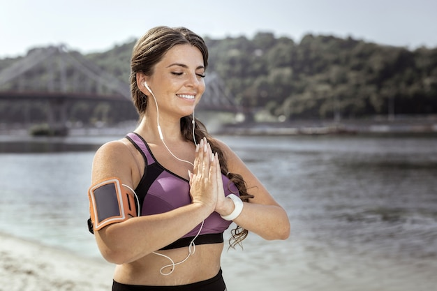 美しい場所。ビーチで瞑想しながら手を合わせてうれしそうな幸せな女性