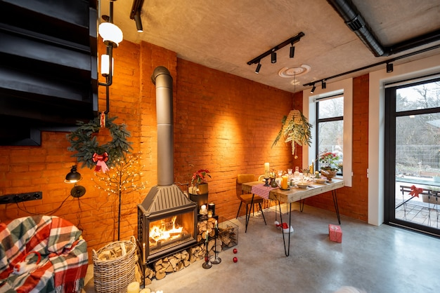 Beautiful loft-style interior with a fireplace and a dining table decorated for the new year holidays