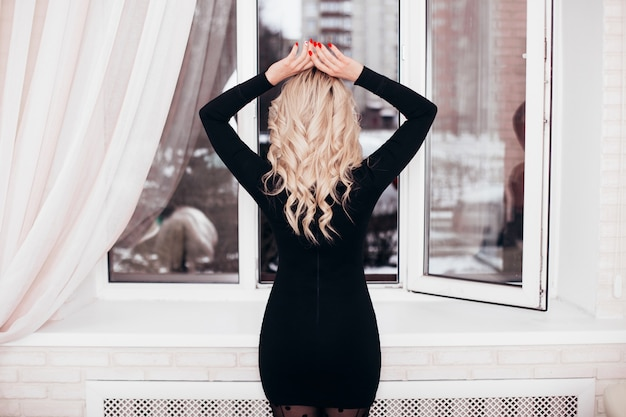 Beautiful lonely blonde woman in black dress looking at the open window