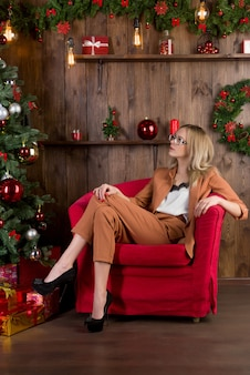 Beautiful lonely woman sits in a red chair near the christmas tree. new year's eve loneliness concept.