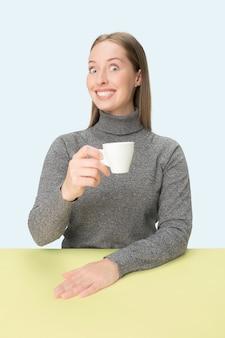 青いスタジオに座って、コーヒーを手に持って悲しそうに見える美しい孤独な女性。ミニマリズムスタイルのクローズアップトーンの肖像画
