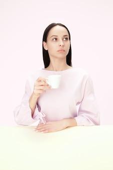 Bella donna sola che si siede allo studio rosa e che sembra triste tenendo in mano la tazza di caffè.