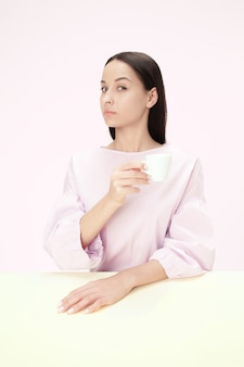 Beautiful lonely woman sitting at pink studio and looking sad holding the cup of coffee in hand.
