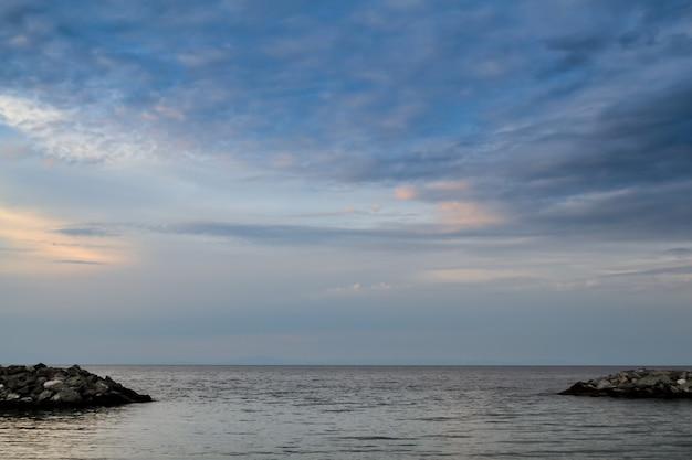 석양에 잔잔한 바다에서 아름 다운 긴 노출 landscapeat. 수평선 근처 바위 장벽