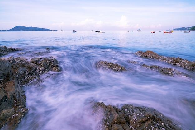 Beautiful long exposure seascape with sea wave forms a dense white foam on the rocks seashore seascape background at phuket thailand.