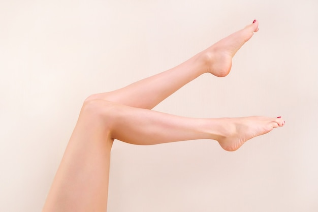 Beautiful long female legs with smooth skin after depilation on a pastel beige