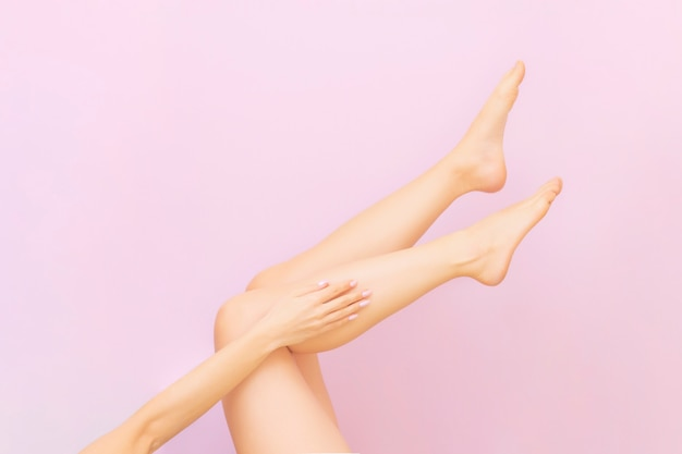 Beautiful long female legs with smooth skin after depilation on pastel pink