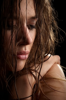 Beautiful long hair brunette woman portrait, wet face, studio shot
