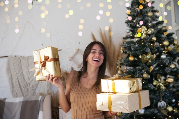 선물 황금 상자를 들고 카메라에 미소 크리스마스 트리 근처 아름다운 장발 소녀