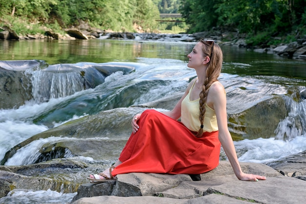 Beautiful long-haired girl in a red skirt sitting on a rock. summer evening. tranquility and enjoyment of nature.