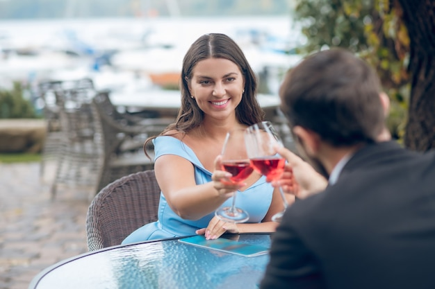 Beautiful long-haired woman in dress and man sitting with glasses of red wine at table in outdoor cafe