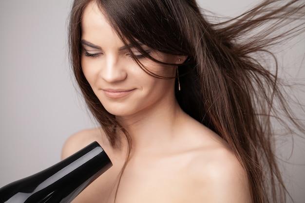 Красивая длинноволосая женщина сушки волос в ванной комнате.