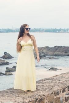 해변에서 긴 드레스에 아름 다운 긴 머리 여자