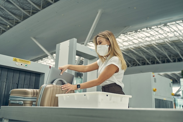 Beautiful long haired woman taking her laptop while putting into plastic box for checkup