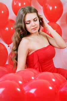 Красивая длинноволосая женщина с большими красными воздушными шарами
